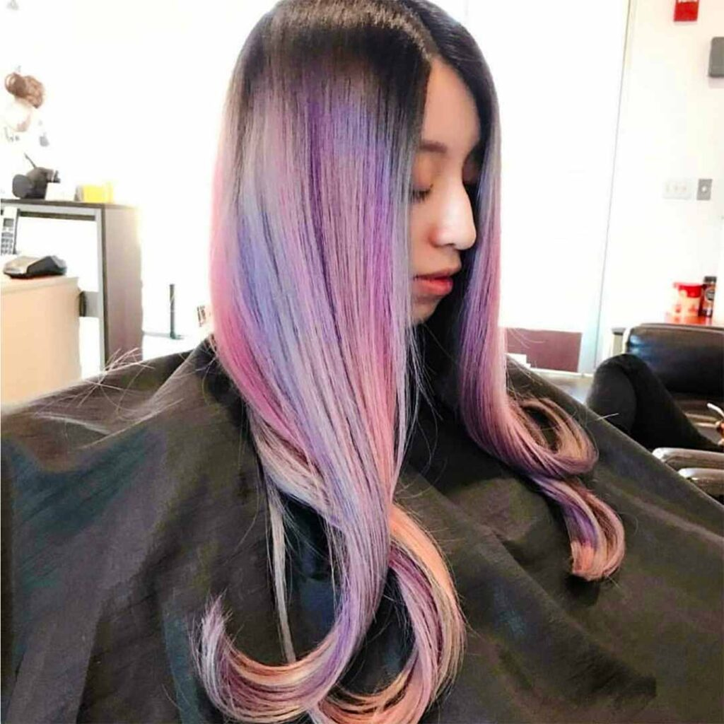 Hair model with colorful hair ranging from purples to pinks and dark naturals at the roots.